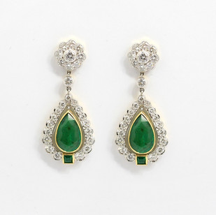 18ct yellow and white gold emerald and diamond drop earrings. The pear cut emeralds 3.69cts, in a fine yellow gold setting are articulated below a cluster of brilliant cut diamonds with a graduated brilliant cut diamond border. The diamonds are G colour, Vs clarity and completed with a square cut emerald feature. £14,000.00