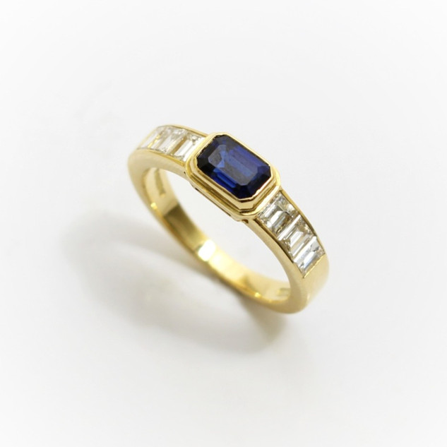 18ct yellow gold sapphire and diamond ring. The central emerald cut sapphire 0.40ct with three graduating baton diamonds to each shoulder. Total diamond weight 0.72ct, G colour, Vs1 clarity. £5,500.00