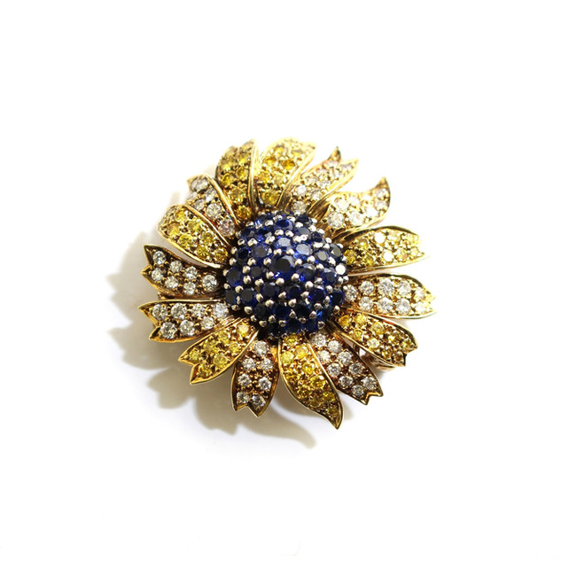 18ct yellow gold diamond, blue and yellow sapphire flower brooch. The brooch measures approximately 3.5cm diameter. Dated 1988. £4,750.00
