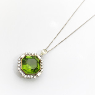 18ct yellow gold and platinum, peridot and diamond pendant. The exceptionally fine octagonal peridot weighing 48.37cts. Completed with a platinum set border of baguette and brilliant cut diamonds totalling 2.30cts. The necklace is finished with an articulated pear cut diamond, 0.72ct set in platinum and suspended below an 18ct yellow gold chain. £12,500.00