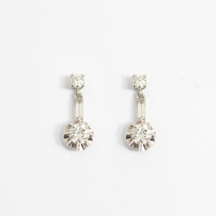 18ct white gold mounted diamond three stone drop earrings. Comprising of a single principle circular brilliant cut diamond within a fancy floral design setting set suspended below a smaller circular diamond and connected by a single baguette cut diamond. Total diamond weight estimated 1.10ct . Post and scroll fittings. £3,850.00