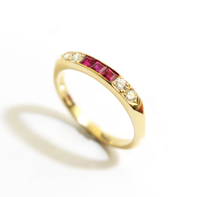 18ct yellow gold ruby and diamond half eternity ring. The three square cut rubies totalling 0.35ct. Total weight of brilliant cut diamonds 0.26ct, G colour, Vs1 clarity. £1,650.00
