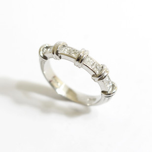 A platinum and diamond half eternity ring. Comprising of princess cut diamonds totalling 0.53ct, G colour, Vs1 clarity with double feature bars between. £2,750.00