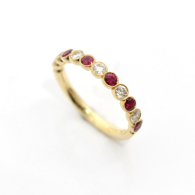 18ct yellow gold ruby and diamond half eternity ring. Comprising of alternating circular rubies and circular diamonds. Total ruby weight 0.54ct, total diamond weight 0.36ct. To a millgrained rub over settings. £2,800.00