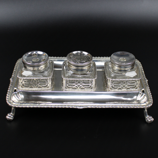 George II ink stand. William Robertson, 1759. Gadroon boarder with pierced bottle holders. 10 ¼ inches by 6 ½ inches Lion claw feet. 24 oz silver. £4,500.00