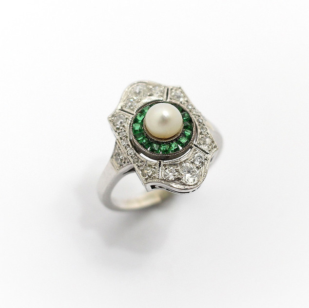 18ct white gold Art Deco pearl, emerald and diamond Art Deco panel ring. Comprising of a central pearl with border of calibre cut emeralds at centre of diamond set panel.  £2,750.00