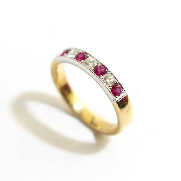 18ct yellow and white gold ruby and diamond millgrain set half eternity ring. Total ruby weight 0.61ct, diamond weight 0.16ct, G colour, Vs1 clarity. £1,650.00