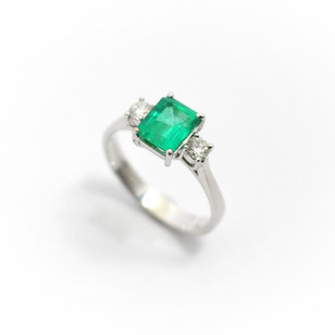 18ct white gold emerald and diamond three stone ring. The central emerald cut diamond 1ct with two circular diamonds 0.10ct each. Claw setting. £2,250.00