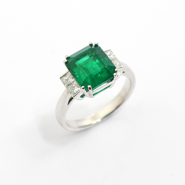 18ct white gold emerald and diamond ring. The central emerald cut emerald 4.47cts, with two princess cut diamonds to either side. Total diamond weight 0.44ct. £12,000.00