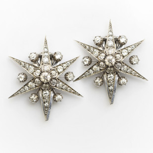 A pair of 18ct white gold and silver star clips. The 18ct white gold stars set with old cut diamonds totalling approximately 8cts. Circa 1900. The later clips are in silver. £8,500.00