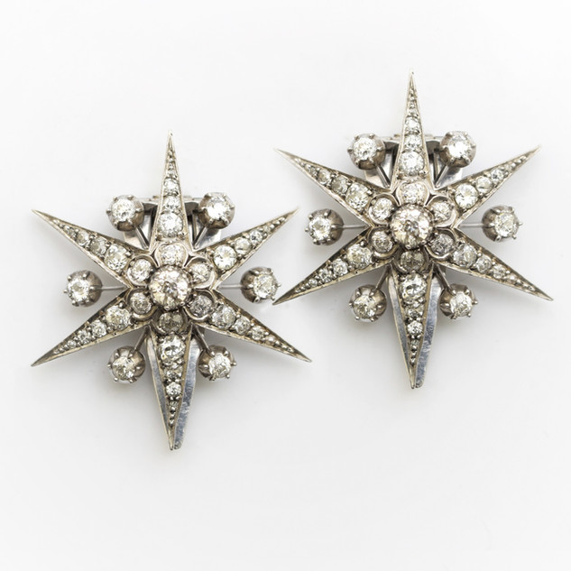 A pair of 18ct white gold and silver star clips. The 18ct white gold stars set with old cut diamonds totalling approximately 8cts. Circa 1900. The later clips are in silver. £9,000.00