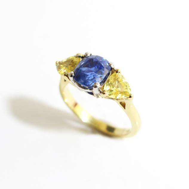 18ct yellow and white gold sapphire three stone ring. The central cushion shaped blue sapphire, 1.05cts and completed with two trillion cut yellow sapphires. £3,500.00