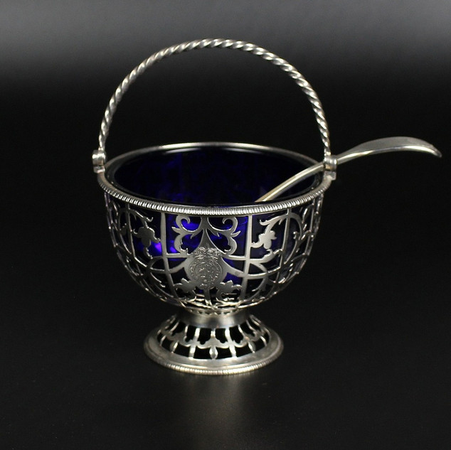 Pierced sugar or cream pail with blue glass liner. Floral pierced rope swing handle   By Edward Aldridge 1771 Weight – 3oz 7 dwt excluding ladle 5 ¼ inches extreme height Engraved with crest of Duchess of Gloucester within garter surmounted with ducal coronet. [Stock number – A112 ] Crest within garter is of the Waldegrave family– Somerset family.   The Waldegrave crest: A plume of feathers issuing from a ducal coronet within garter and ducal coronet above.   Maria Walpole, the granddaughter of Robert Walpole (first Prime Minister of the UK 1721 -41) grew up in Frogmore House, Windsor. In 1759 she married James Waldegrave, Second Earl Waldegrave, who died in 1763. In 1766 she married Prince William, Duke of Gloucester & Edinburgh, at her home in Pall Mall.   Ladle fiddle thread and shell Salt ladle George Addams 1845 £1,850.00