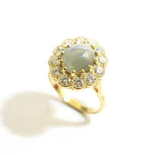 18ct all yellow gold mounted Chrysoberyl 'cats eye' and diamond cluster ring. The cabochon cats eye of attractive moss green colour and completed with border of circular brilliant diamonds totalling 1.35cts. Grey-Harris & Co commission. £5,250.00