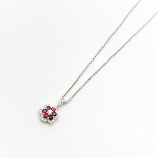18ct white gold ruby and diamond flower pendant. £1,400.00