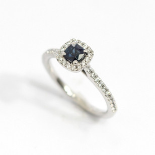 A platinum and 18ct white gold sapphire and diamond cluster ring. The central cushion cut sapphire, 0.31ct. Completed with a surround of round brilliant cut diamonds and diamond set shank. Total diamond weight 0.25ct. £1,850.00