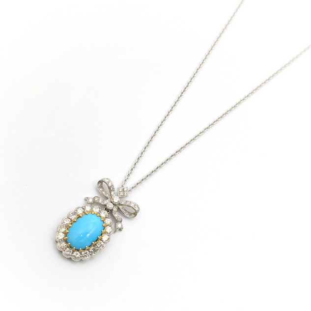 18ct white and yellow gold turquoise and diamond pendant. A fine example of early turquoise, set within yellow gold setting and completed with brilliant cut diamond border below a diamond bow. Complete with a 18ct white gold chain and fitted case. £5,500.00