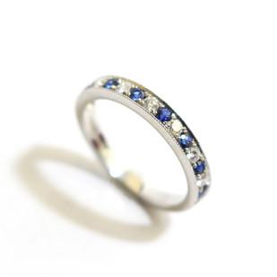 A platinum sapphire and diamond millgrain set half eternity ring. Total sapphire weight 0.30ct, diamond weight 0.20ct, G colour, Vs1 clarity. £1,500.00
