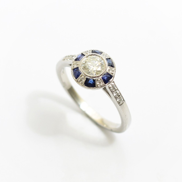 Platinum solitaire diamond ring with calibre cut sapphires. The central modern brilliant cut diamond 0.55ct, G colour, Vs1 clarity. Millgrain set with a border of alternating diamonds and sapphires and completed with diamond set shoulders. £3,500.00