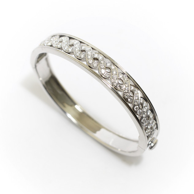 18ct white gold diamond set hinged bangle. The top section comprising of a diamond set lattice form with solid border above and below. Total diamond weight 2.11cts, exceptionally fine quality. By D A Soley Ltd London. £12,500.00