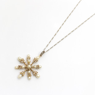 A late Victorian gold and silver fronted pendant. The pendant of snowflake design set with natural pearls and diamonds. Very fine condition on a figaroo chain. £2,750.00