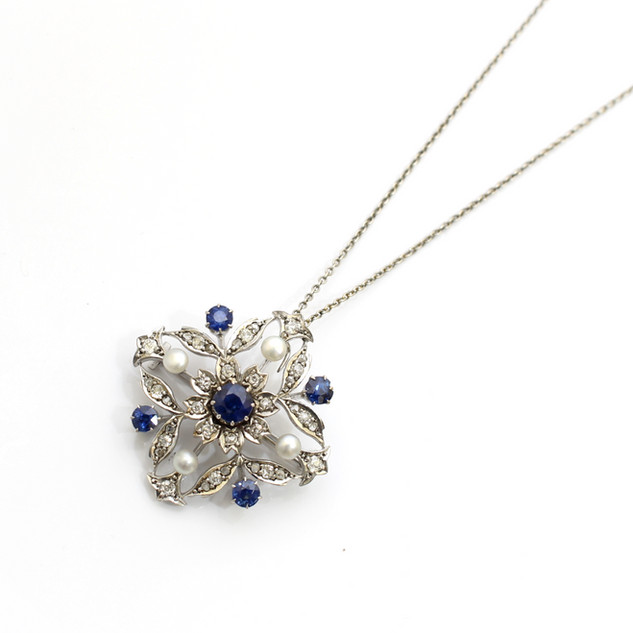 A platinum mounted sapphire,  diamond and pearl pendant with provision for wear as a brooch. Circa 1900. Completed with a detachable platinum chain.  £3,500.00