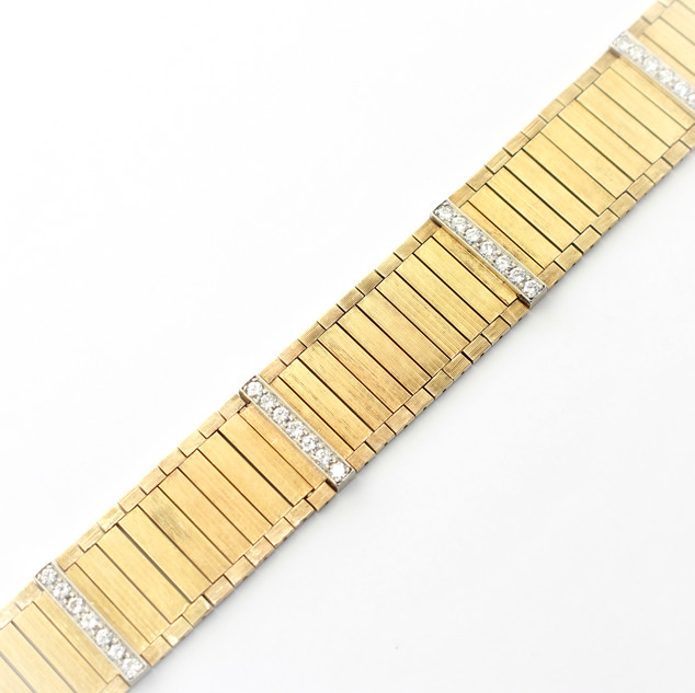14ct yellow gold diamond dress bracelet. Comprising of matt finished textured flat articulated links. Completed with straps of circular diamonds. North American. Circa 1975.