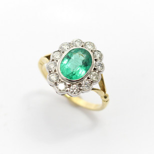18ct yellow and white gold emerald and diamond oval cluster ring. The central oval emerald 1.63ct, with border of well matched circular modern brilliant cut diamonds totaling 0.70ct. Shaped scallop edge setting completed with forked channel shoulders. £3,250.00