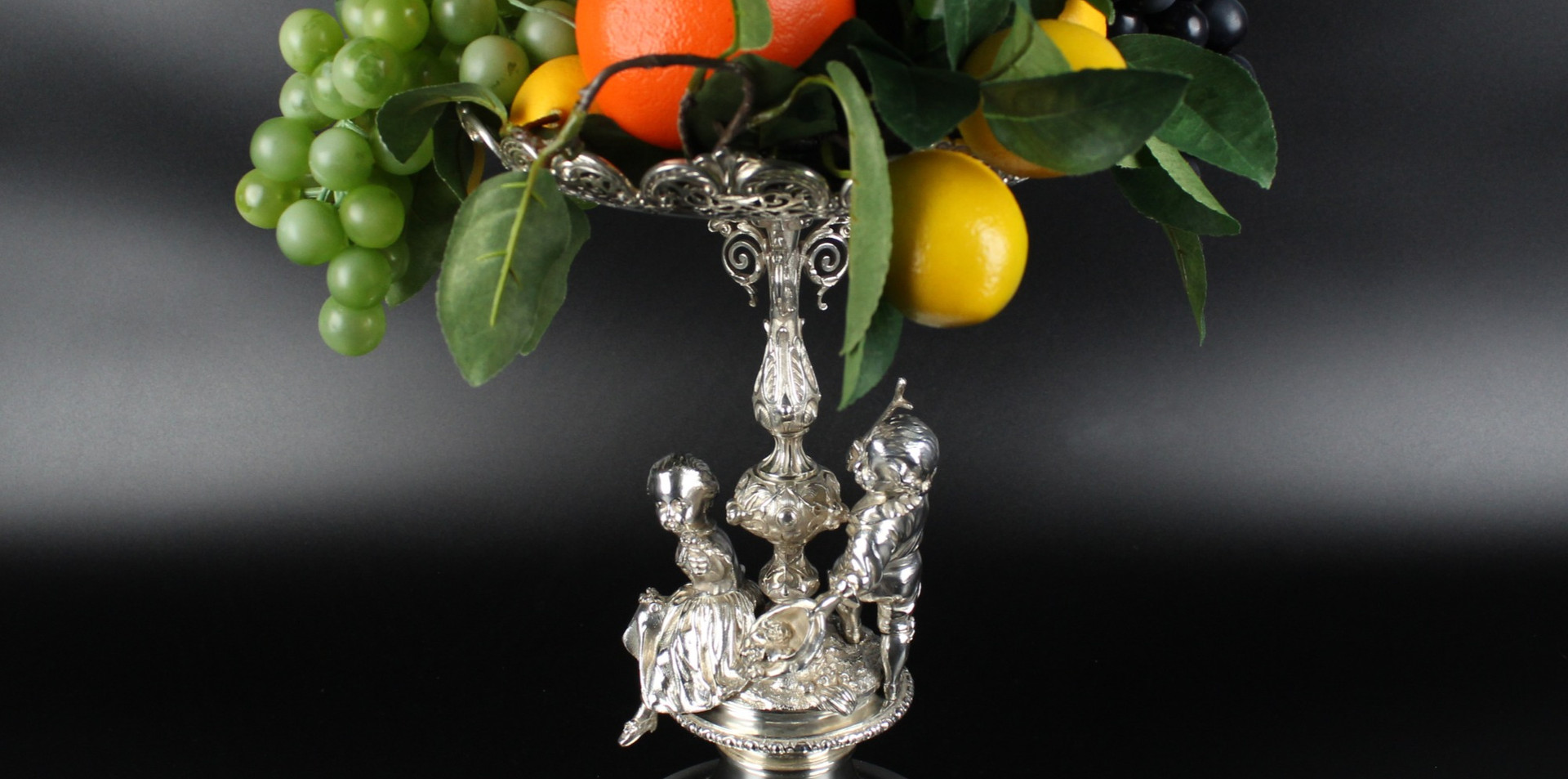 """Silver centrepiece 13"""" high Robert Garrard II, 1872. 60 oz. Engraved around base R & S GARRARD LONDON"""" The crest and motto For the Rev. John Yonge of Puslinch & Combe, Devon. Motto QUALIS VITA FINIS ITA - As Life so its end  The centrepiece with a scene of children - The girl making a  garland of roses, her playmate offering his cap full of roses to her.  £4,500.00"""