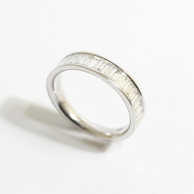 A platinum and diamond half eternity ring. The baguette cut diamonds totalling 0.87ct. £3,650.00