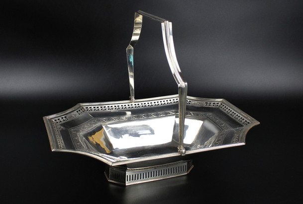 Irish Bread Basket Dublin 1795   John Stoyte Rectangular with incurved corners reed boarder. Pierced gallery with engraved oval panels. Central floral engraved oval. Pierced foot Shaped reed swing handle   32 oz Length – 14 ½ inches £2,650.00