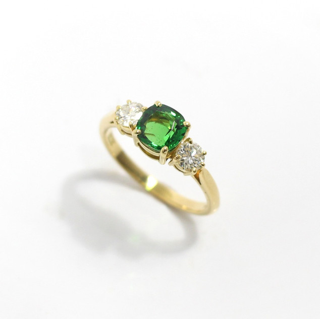 18ct yellow gold tsavorite and diamond three stone ring. The central cushion cut tsavorite 1.10cts, with modern brilliant cut diamonds totalling 0.44ct, G colour, Vs clarity. £5,000.00