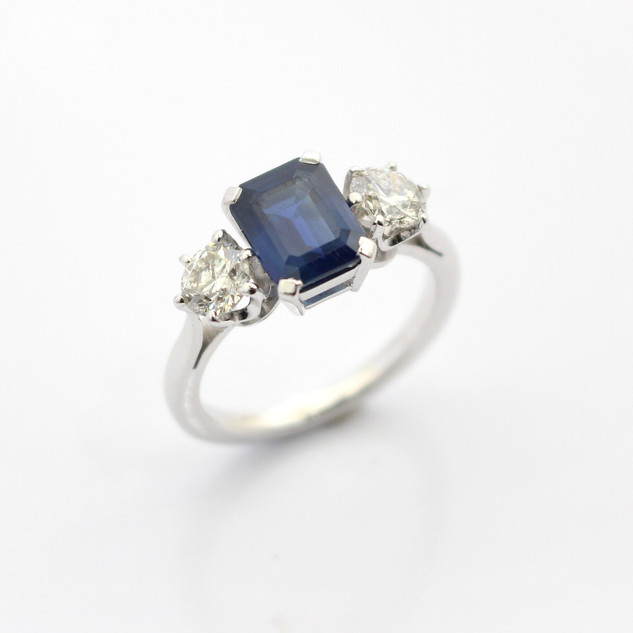 A platinum mounted sapphire and diamond three stone ring.  The central emerald cut sapphire 1.88cts, set with two circular modern brilliant cut diamonds, 0.50ct each. Estimated K colour, Si2/Pique clarity. In a high quality coronet claw setting. £6,750.00