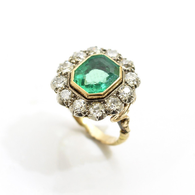 Austro-Hungarian Victorian copy of a Gerogian ring. The ring comprising of a central emerald cut emerald approximately 3.24cts in a yellow gold rub over setting. The fine emerald is surrounded by twelve old cut diamonds with an estimated total weight 2cts. 18ct yellow gold mounted and silver fronted to a scrolling yellow gold shank. £12,500.00
