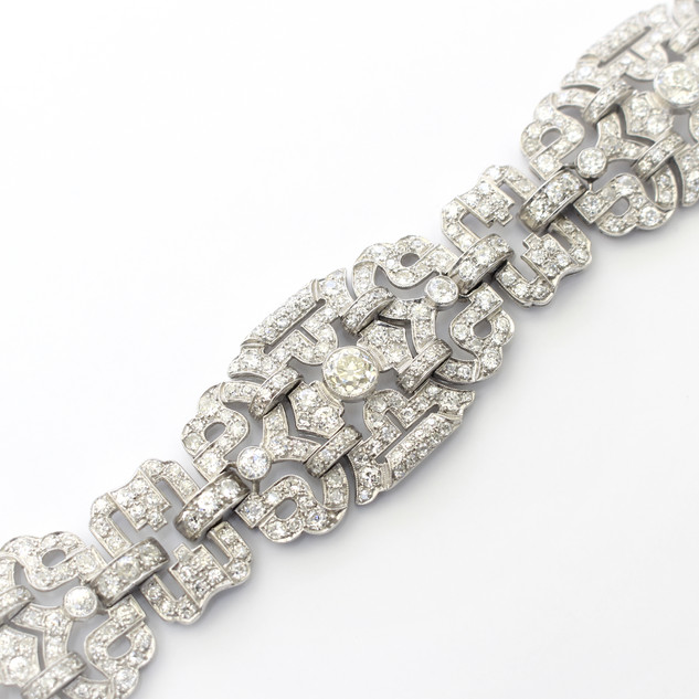 Platinum Art Deco diamond panel bracelet. Comprising of three matched diamond set panels with larger old cut diamond at centre. The diamonds of circular old cut and early modern brilliant cuts.  The three panels conected by diamond set articulated links. Total diamond weight 22cts. Circa 1930.  £22,000.00