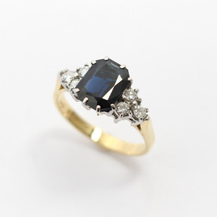 18ct yellow and white gold sapphire and diamond ring. The central sapphire, 1.88cts with trefoil of brilliant cut diamonds to either side. £875.00