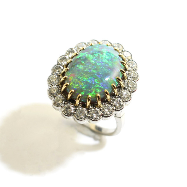A platinum and 18ct yellow gold opal and diamond cluster ring. The fine black opal, 12.50cts and completed with surround of circular brilliant diamonds totalling 3.15cts, G, Vs. £14,000.00