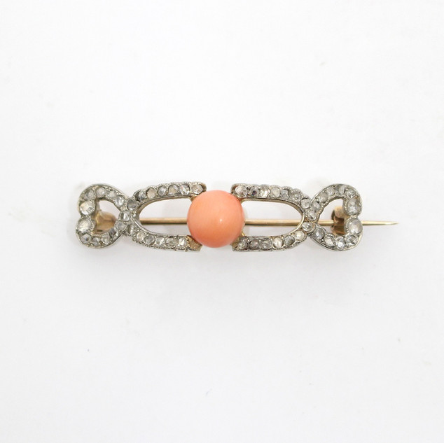 An early coral and old cut diamond brooch. Almost in the form of a buckle, of small size and set in gold. £425.00