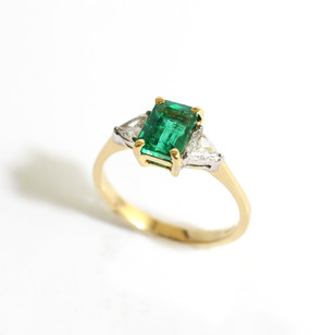 18ct gold mounted emerald and diamond three stone ring. The central emerald cut emerald of fine colour, 1.08cts. Completed with two trillion shaped diamonds at 0.25ct each. £3,250.00
