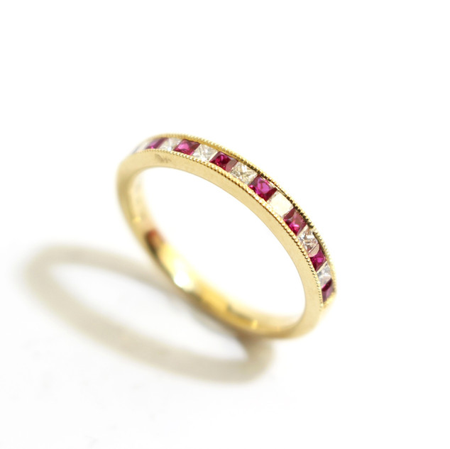 18ct yellow gold ruby and diamond millgrain set half eternity ring. £1,250.00
