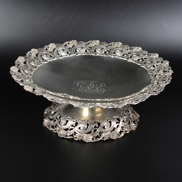 North American Cake Stand with extravagant pierced and chaste boarder, repeated on foot.  Extravagant floral monogram present.  Makers mark – lions head with tail   36 oz 12 inches  £ 1200.00