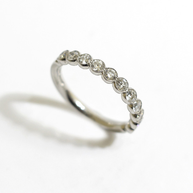 A platinum and diamond half eternity ring. The brilliant cut diamonds totalling approximately 1ct, in a scallop millegrain setting. £2,450.00