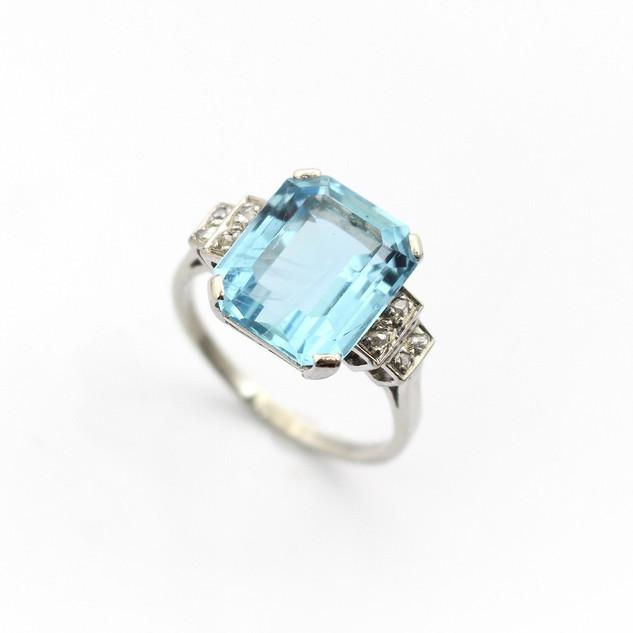 18ct white gold aquamarine and diamond ring. The emerald cut aquamarine 6.50cts, with rose cut diamond stepped shoulders. Circa 1950. £4,250.00