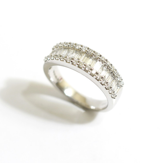 A platinum and diamond half eternity ring. Comprising of a central strap of baguette cut diamonds with frame of brilliant cut diamonds. Total diamond weight 1.10cts. £3,250.00