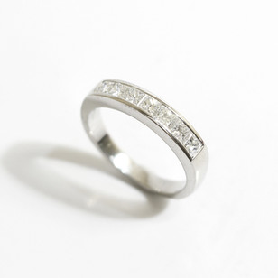 A platinum and diamond half eternity ring. The princess cut diamonds totalling 0.71ct, G colour, Vs clarity. £2,750.00