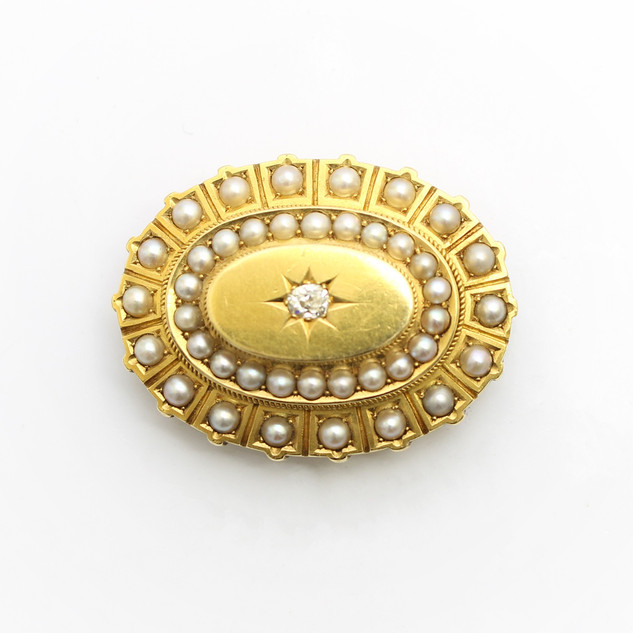 A Victorian 15ct yellow gold mourning brooch. Set with a diamond central feature and surrounds of seed pearls. £650.00