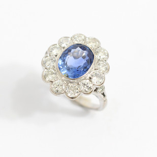 18ct white gold sapphire and diamond cluster ring. The central oval pale sapphire, 2.75cts. Completed with a border of brilliant cut diamonds totalling 1.50cts. £6,000.00