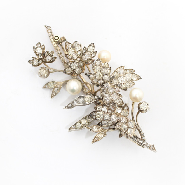 "A Victorian diamond and natural pearl set brooch.The brooch comprising of rose cut diamonds set in 18ct yellow gold and silver fronted and completed with three natural pearls. The brooch 3"" x 1.5"". £4,750.00"