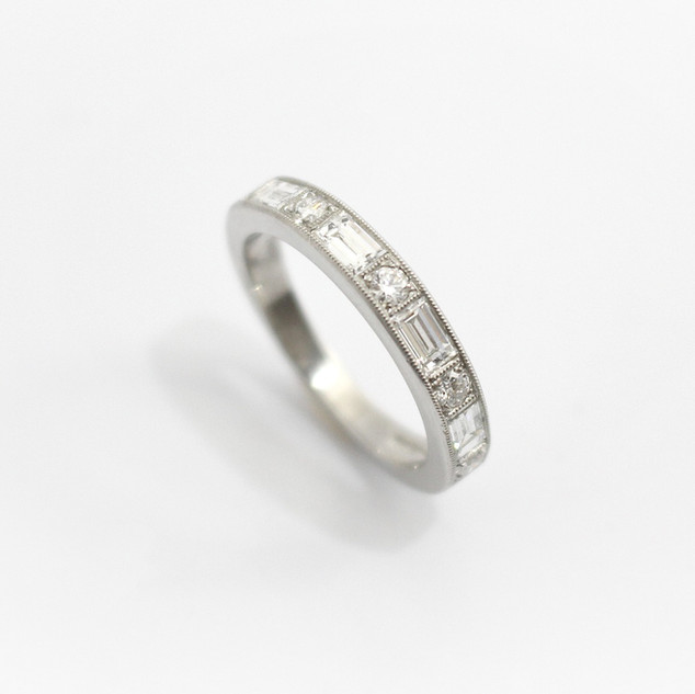 Platinum and diamond half eternity ring. Comprising of alternating baguette cut diamonds and circular modern brilliant cut diamonds.The total weight of baguette cut diamonds 0.56ct, and rounds 0.21ctct. In a millgrained channel settings. £2,900.00