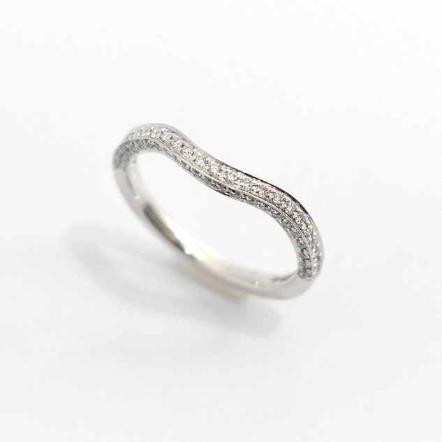 A platinum mounted diamond set wish bone eternity/wedding ring. Uniquely set on two sides, total diamond weight 0.25ct. In a channel setting. £1,650.00